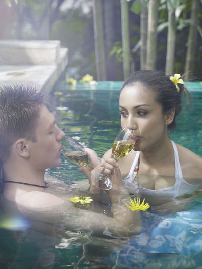 Close-Up Of Couple Having Drink In Swimming Pool