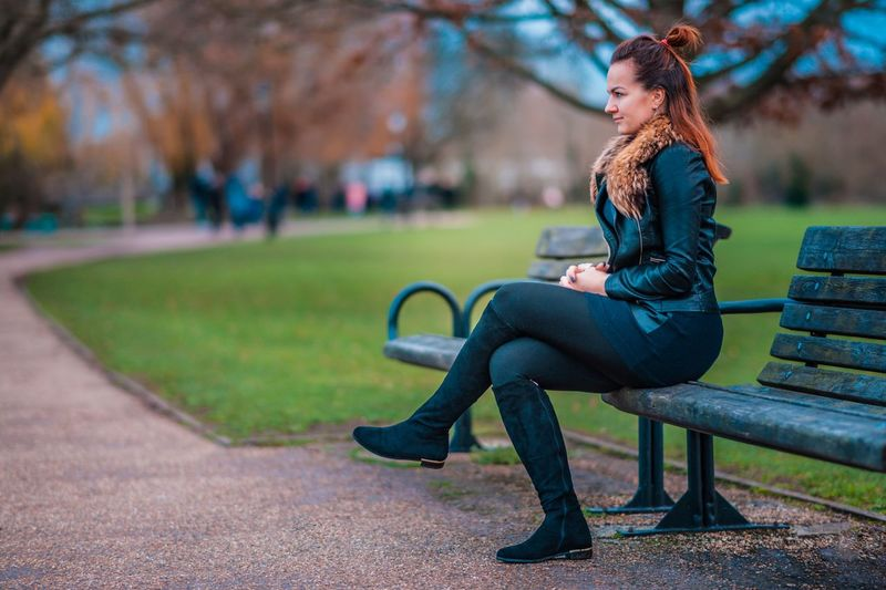 Side view of thoughtful young woman sitting on bench at park