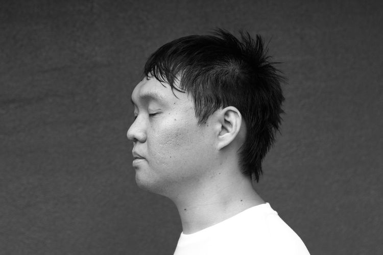 Side View Of Thoughtful Man With Eyes Closed Against Wall
