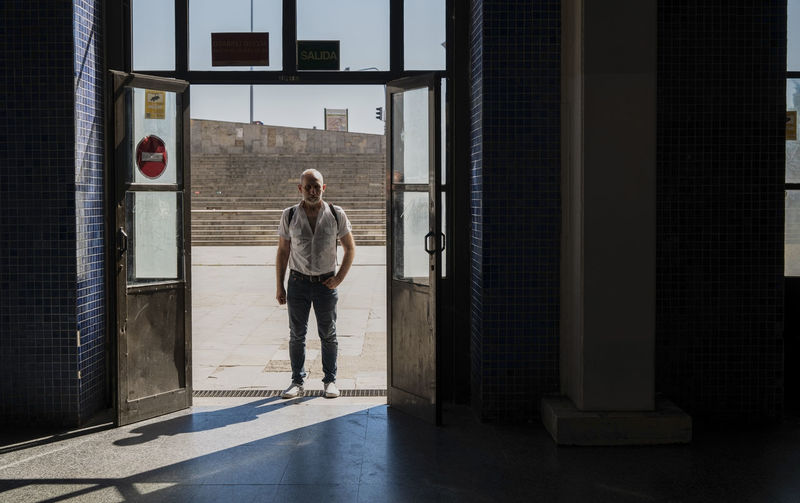 Full length of man standing at the entrance of a station in city