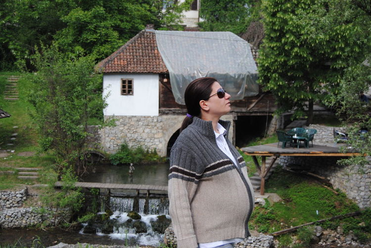 Pregnant woman wearing sunglasses and jacket standing against house