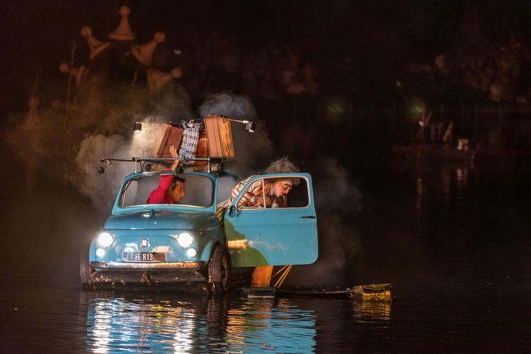 Abandoned boats in water at night