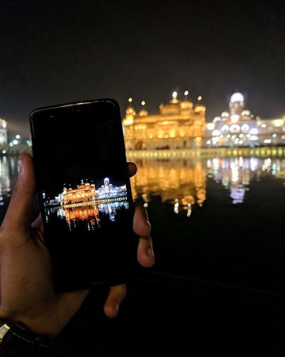 Cropped hand photographing with golden temple on phone at night