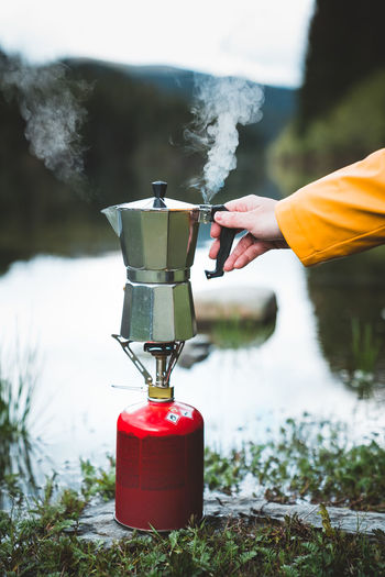 Cropped hand holding coffee maker on camping stove