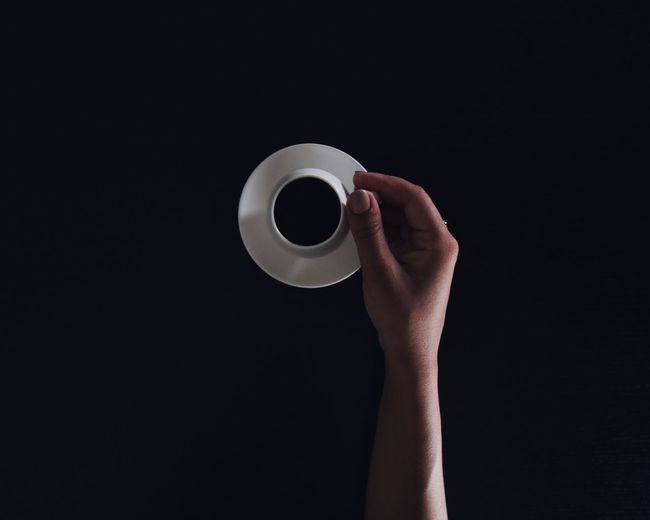 Cropped hand holding coffee cup on black background