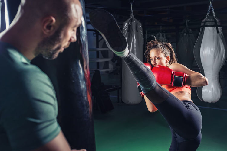 Young female boxer practicing with coach in gym