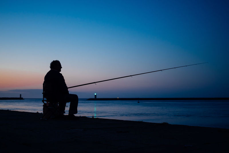 Silhouette man fishing in sea against blue sky during sunset