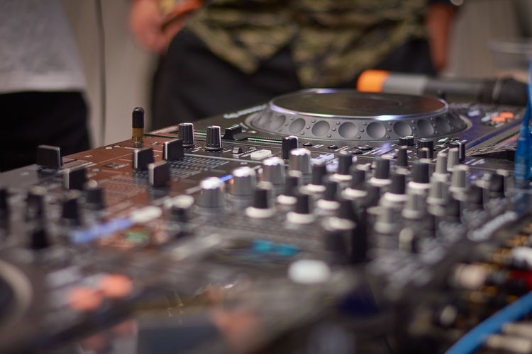 Midsection of dj playing music in club