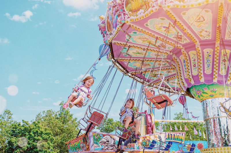 People in amusement park against sky