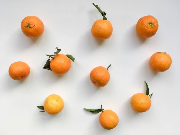 High angle view of orange and fruits on white background
