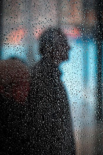 Shadow of men on wet window at home