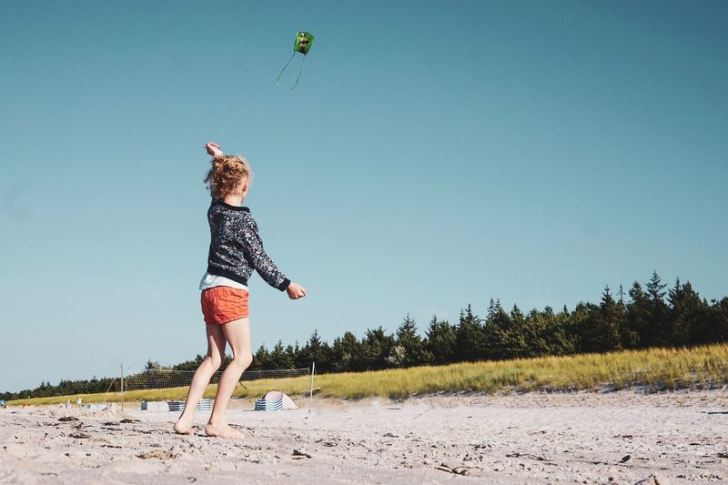 Girl Flying Kite Against Clear Blue Sky