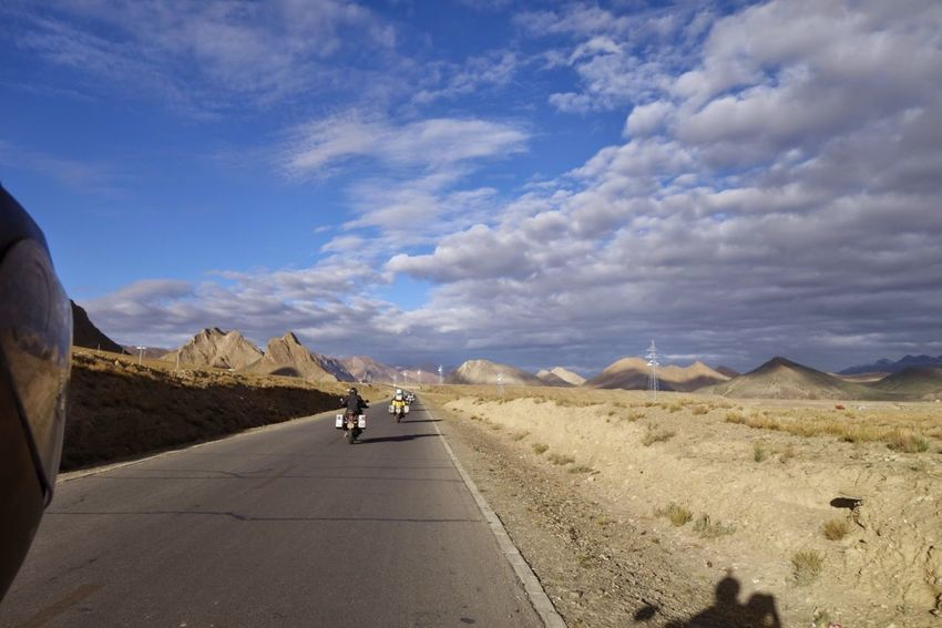 Riding through Tibet, China. Adventure Arid Climate Beauty In Nature Cloud - Sky Day Desert Domestic Animals Land Vehicle Landscape Lifestyles Mammal Men Mode Of Transport Motorcycle Mountain Nature One Person Outdoors Real People Road Scenics Sky The Way Forward Transportation Travel Destinations