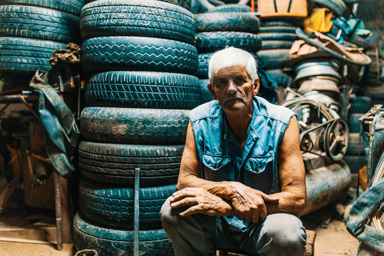 Portrait of man sitting by tires at garage
