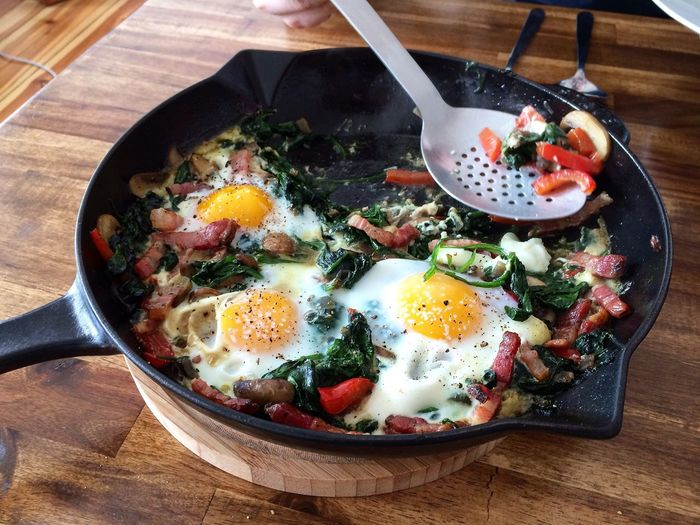 Fried eggs with vegetables in pan