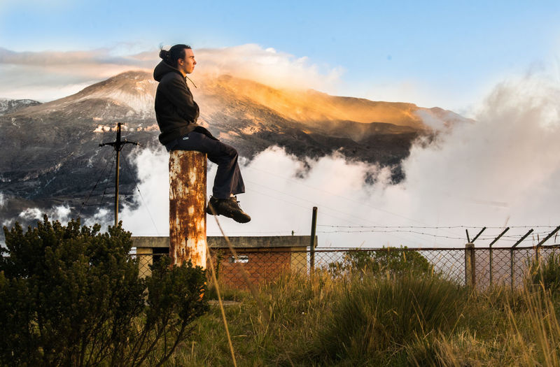 Full length side view of man sitting on metallic rod against mountain