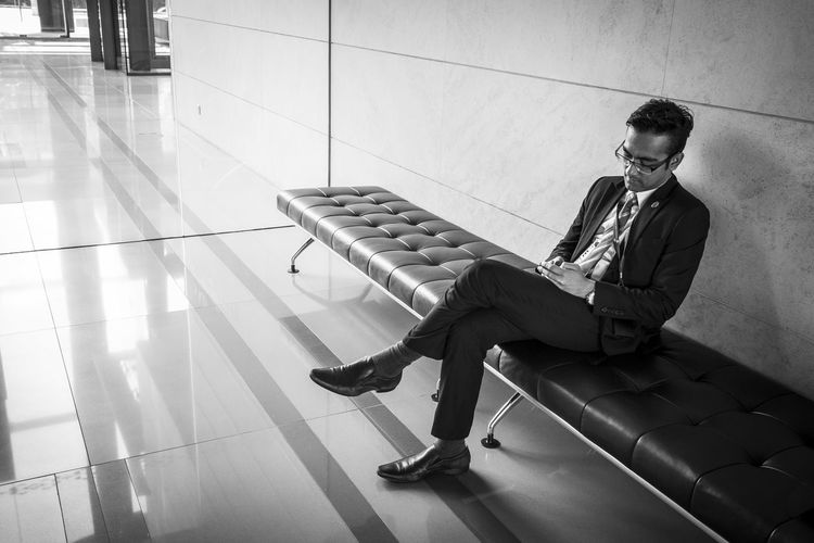 Man in business suit sitting on a bench looking at his mobile phone Asian Male Bench Black & White Bored Businessman Glasses Lifestyles Male Man Mobile Monochrome Photography Perspectives Relaxation Sitting Suit Suit And Tie Waiting Young Adult