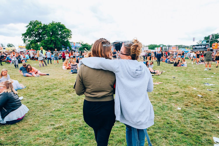 Rear view of friends walking on grass in musical festival