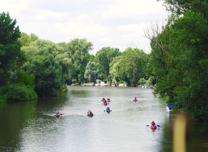 People Canoeing In River Against Sky