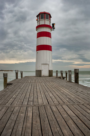 Lighthouse Jetty Wood Paneling Pier Water Outdoors No People Direction Safety Lighthouse Tower Cloud - Sky Architecture Guidance Security Protection Sky Built Structure Winter Ice
