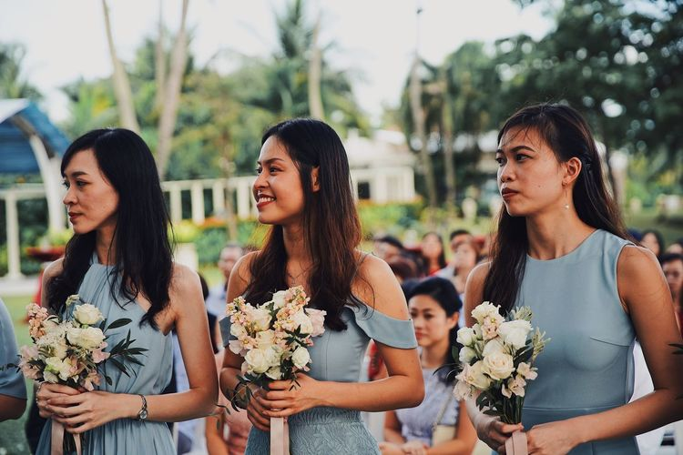 Women standing by flowering plants