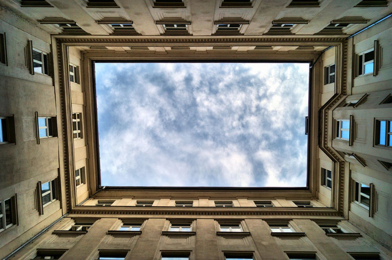 Patio and low angle view of building against sky