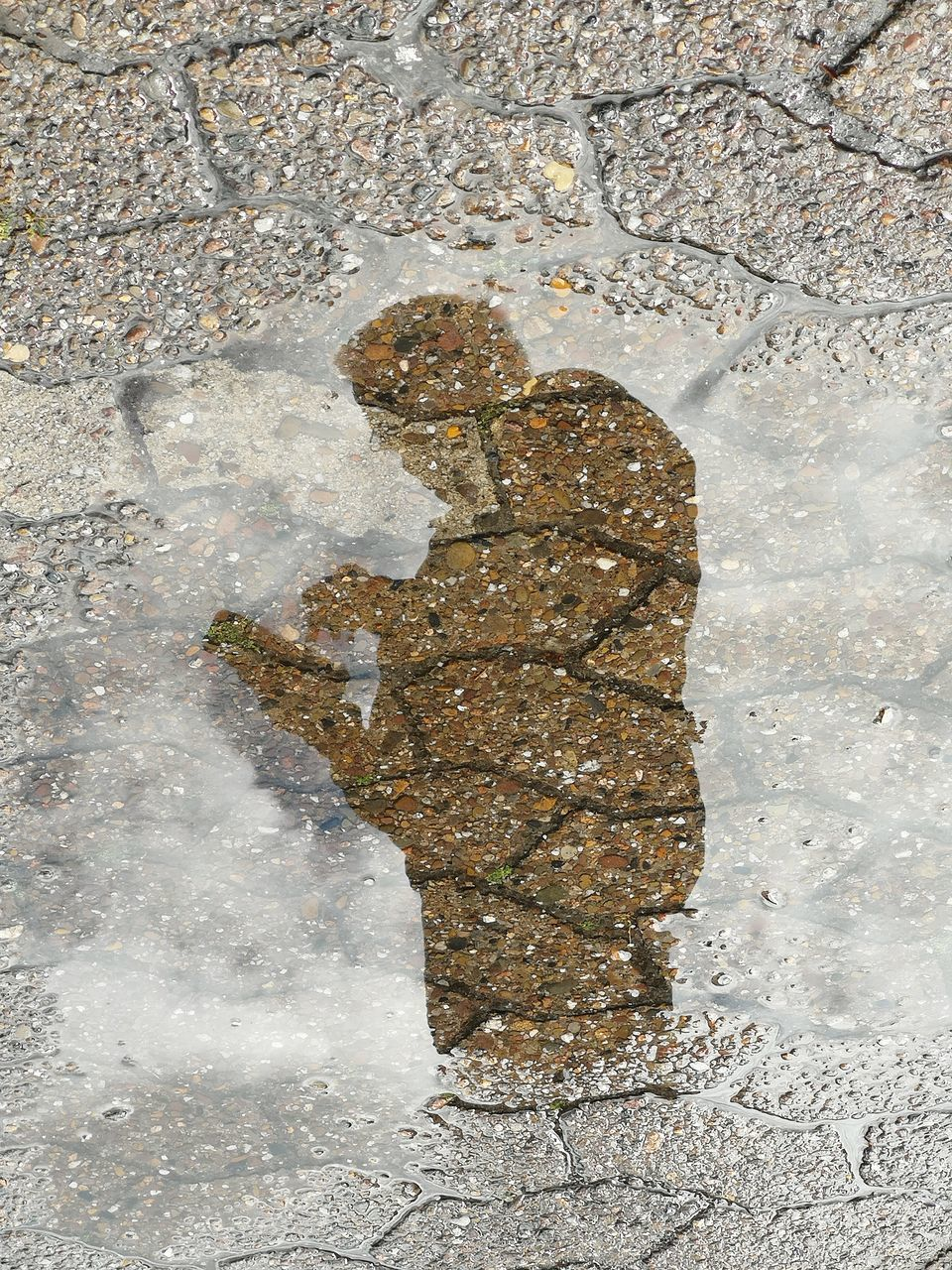 HIGH ANGLE VIEW OF MAN STANDING IN PUDDLE