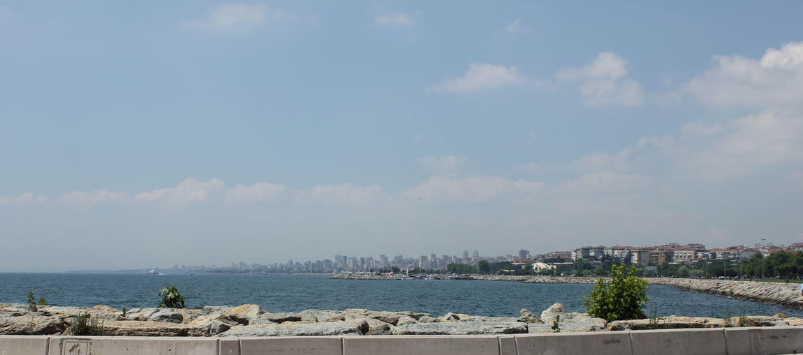 Panoramic view of city by sea against sky