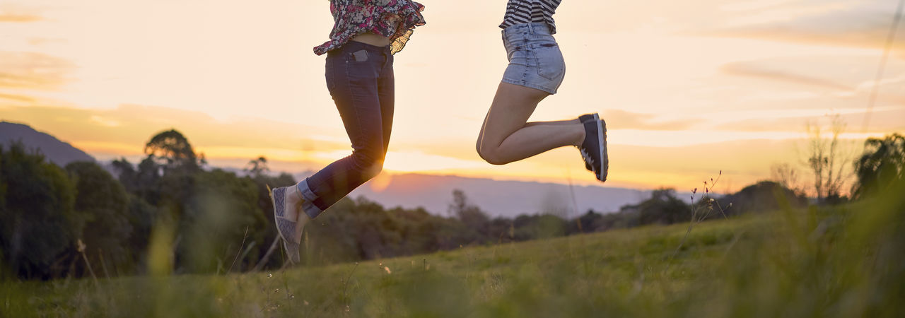 Low Section Of Friends Jumping Over Field Against Sky