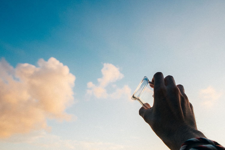 Low angle view of man with glass against sky