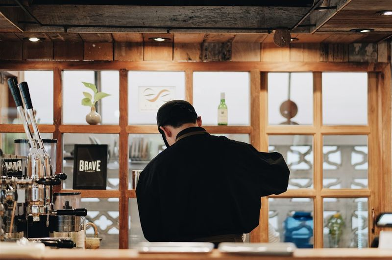 Rear view of barista working in caf