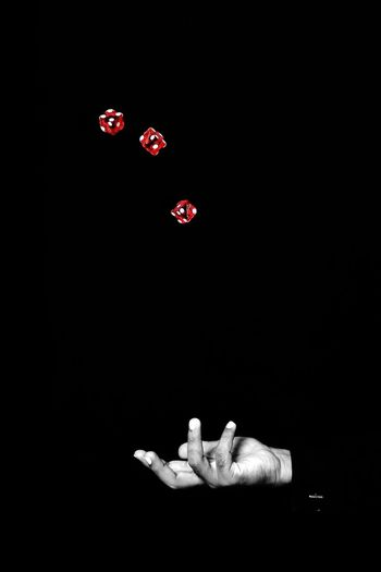 Cropped hand of man with dices in mid-air against black background