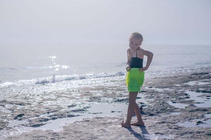 Full Length Portrait Of Cute Girl Standing At Beach Against Sky