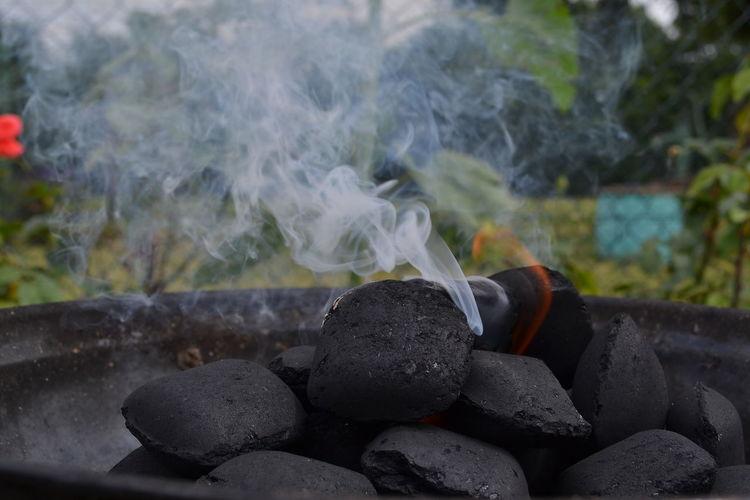 Close-up of burning coals emitting smoke