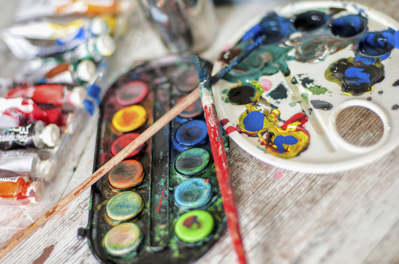 High angle view of messy palette with paintbrushes on table