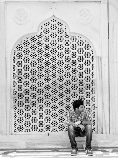 Full Length Of Man Sitting Against Patterned Wall At Taj Mahal