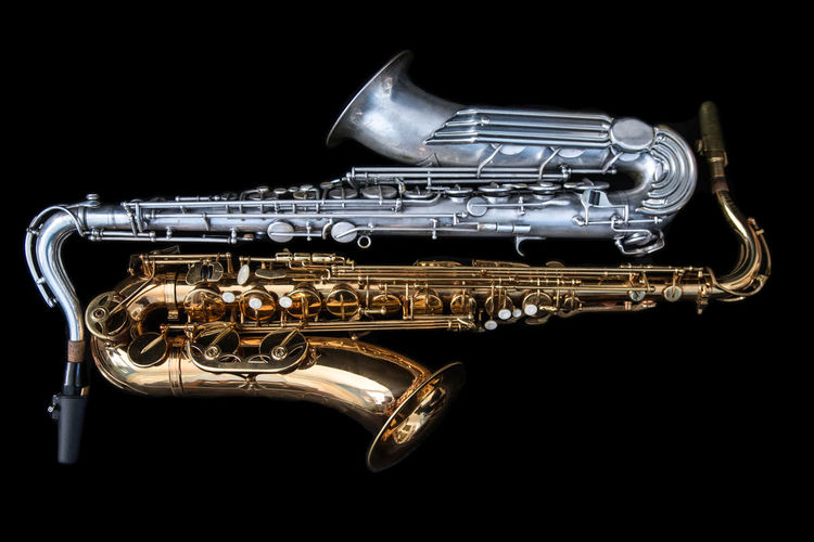Two saxophones lying down. Sax Arts Culture And Entertainment Black Background Brass Brass Instrument  Close-up Gold Colored Indoors  Lying Down Metal Music Musical Instrument No People Saxophone Shiny Silver Colored Studio Shot Two Two Objects Wind Instrument