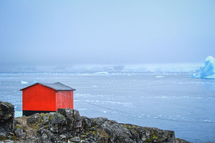 Red building by sea against sky