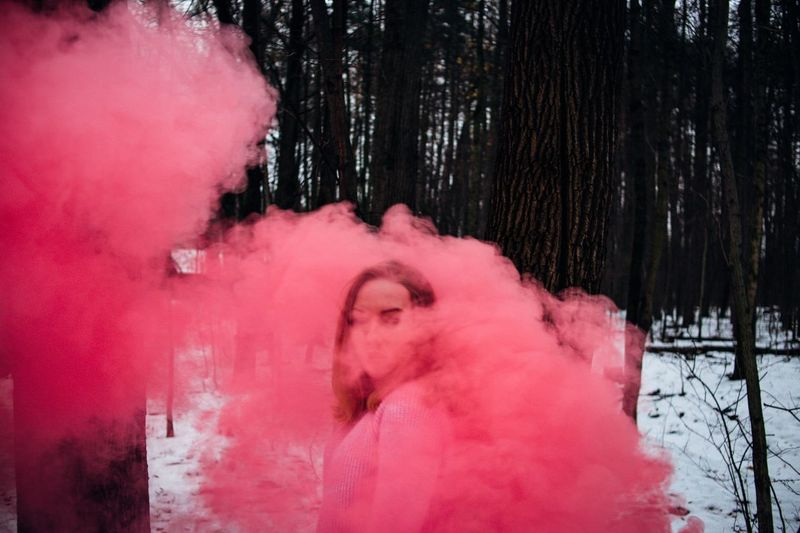Young woman with smoke bomb standing in forest during winter