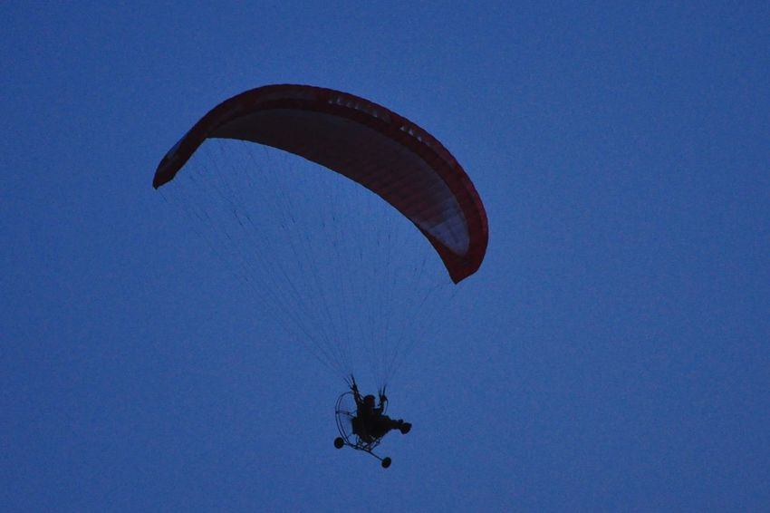 Flying Extreme Sports Paragliding Parachute Mid-air Silhouette Adventure Sky Day Outdoors Pilot People Clear Sky Nature One Person Stunt Person