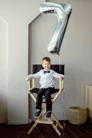 Photo session with a ballon 7 years old. silver ballon with number 7. a boy at a photoset