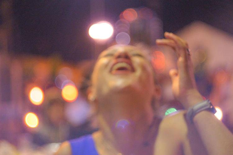 Defocused image of happy woman laughing at night