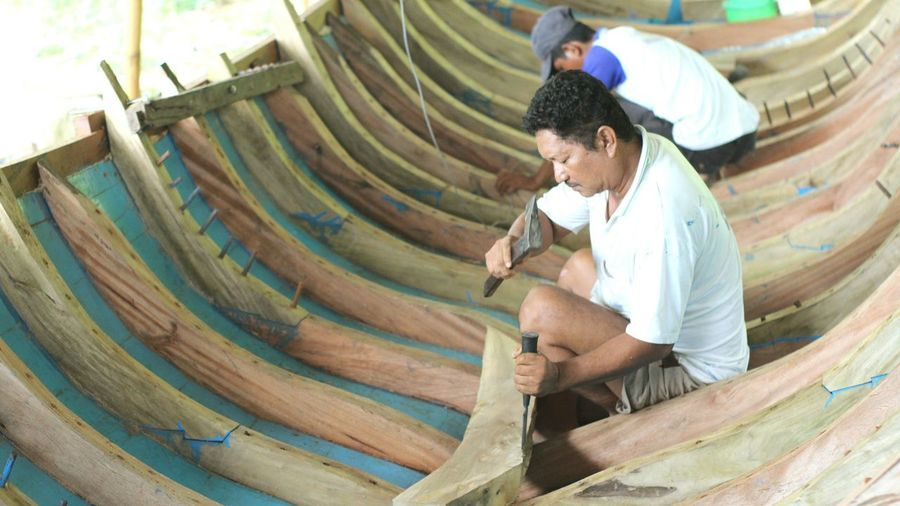 Side view of male workers making wooden boat