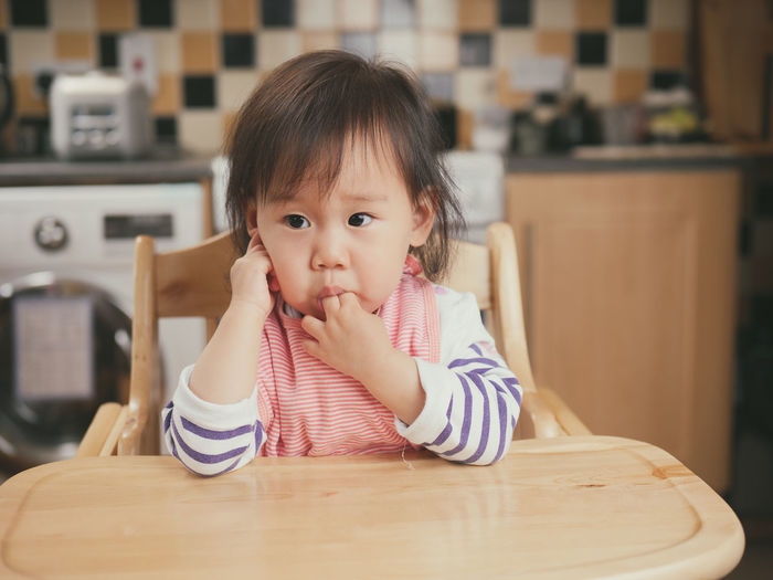 Baby girl with fingers in mouth sitting on high chair at home
