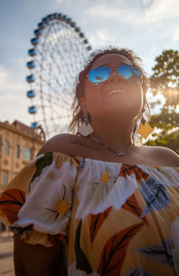 Midsection of woman wearing sunglasses standing against sky