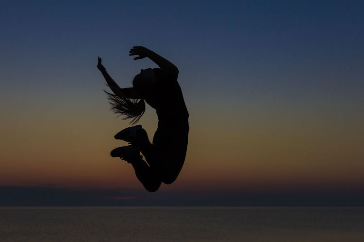 Silhouette Woman Jumping Over Sea Against Sky During Sunset