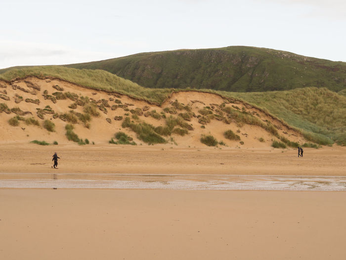 Couples walking alongside some of the biggest sand dunes in Europe Beach Walking, Lovers, Lovers Walking, Sand Dunes, Large Sand Dunes, Lovers Walking Beach Walking Donegal Ireland Landscape Peaceful Walking Sand Sand Dune Tranquil Scene