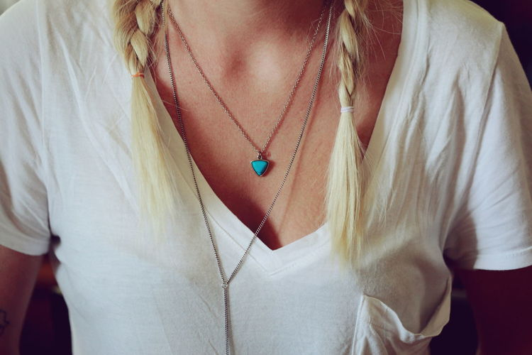Midsection of woman with braided hair wearing hear pendant necklace