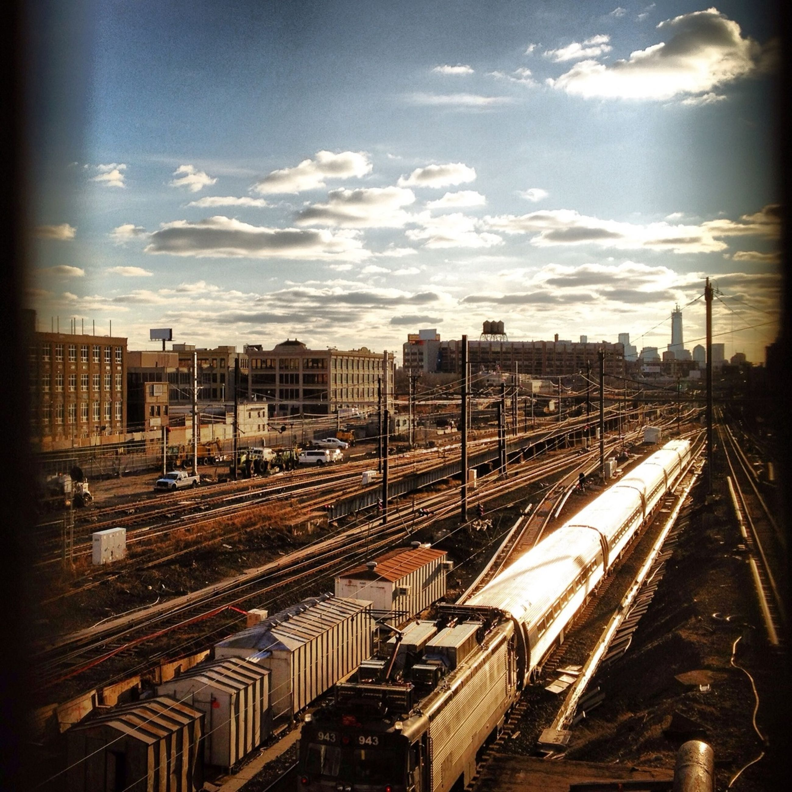 railroad track, architecture, transportation, built structure, rail transportation, public transportation, railroad station, building exterior, railroad station platform, sky, city, high angle view, train - vehicle, cloud - sky, travel, mode of transport, diminishing perspective, city life, cityscape, train