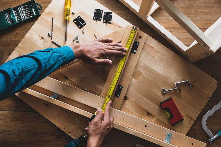 Cropped hands of carpenter measuring wood